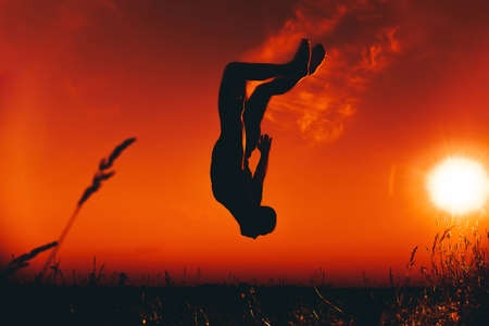 silhouette of a male athlete jumping and doing somersaults