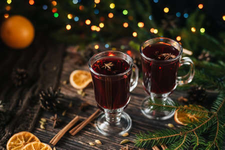 glasses with mulled wine on a wooden table decorated with a Christmas trees. Traditional winter alcoholic drink with orange slices Stok Fotoğraf