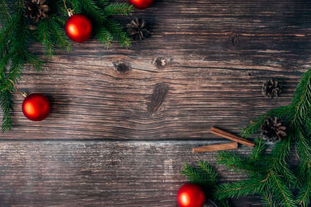 Christmas wooden background with fir branches, red balls and cones