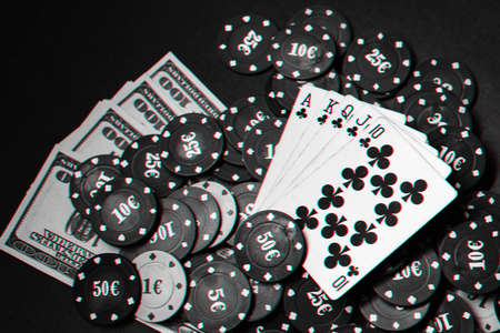 cards with a Royal flush on a pile of chips and money dollars in a game of poker