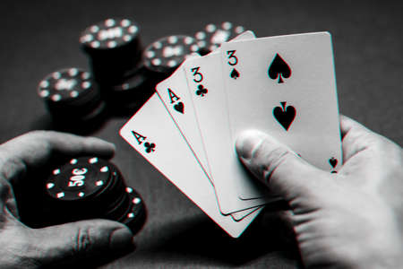 Playing poker in the casino. Cards with two pairs in the hand of the player making a bet with chips