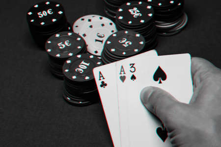 cards with one pair of aces in the hands of a poker player in a casino on the background of a table with chips