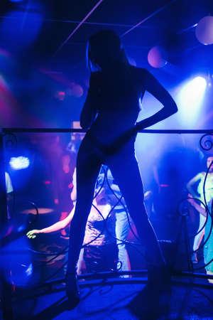 girl go-go dancer posing in a nightclub on stage