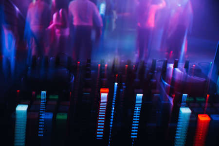 DJ mixer in a nightclub with a background of glowing lights from buttons Stok Fotoğraf
