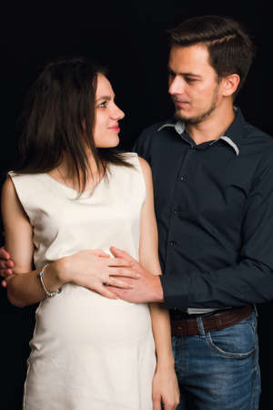 Happy pregnant wife and husband hugging on black background. The concept of a young family