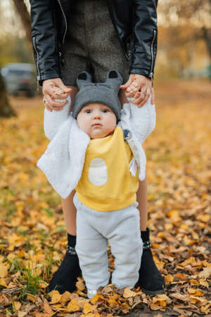 little baby boy learns to take first steps holding moms hands in autumn