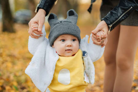 little baby boy holding moms hands in autumn