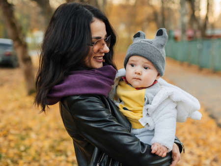 young beautiful Caucasian girl mom smiling and holding her little boy son Stok Fotoğraf