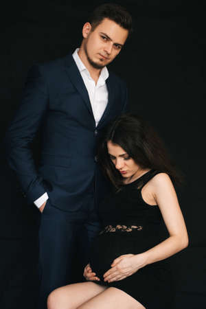 stylish Caucasian man and his young pregnant girl hugging Stok Fotoğraf