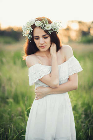 attractive Caucasian brunette girl in white dress and with wreath Stok Fotoğraf