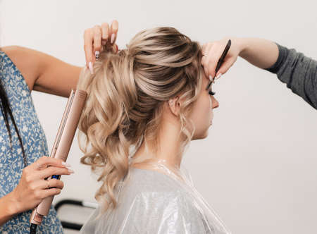 a hairdresser and a make-up artist simultaneously do their hair and make-up in a professional salon