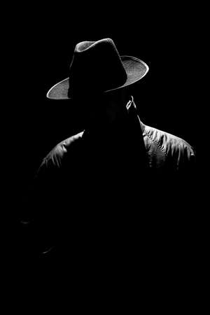 dark mystical silhouette of a man in a hat at night