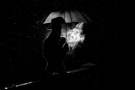 silhouette of a man in a hat under an umbrella Smoking a cigarette at night in the rain in the city