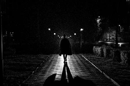 dramatic silhouette of a man in a hat and raincoat walking through the city at night Banque d'images
