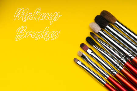 Red makeup brushes on yellow background Imagens