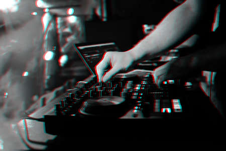 DJ mixes music on a professional controller Board in a nightclub at a party