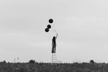 surreal photo of a girl in a hat with balloons in her hand