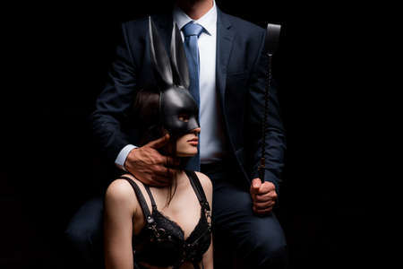 dominant man with a whip Flogger and a submissive girl in handcuffs and a face mask