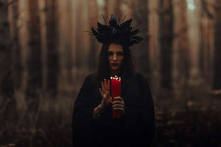 dark terrible witch with candles in her hands performs an occult mystical ritual Reklamní fotografie