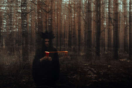 witch in a black costume with candles in her hands performs an occult ritual and mystical spells in a dark forest Stock Photo