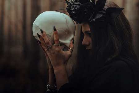 portrait of a terrible witch with a skull in the hands of a dead man performs an occult mystical ritual Reklamní fotografie