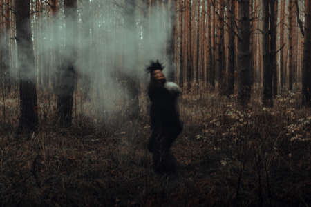 blurred silhouette of a terrible witch with a skull in her hands performing a mystical occult satanic ritual