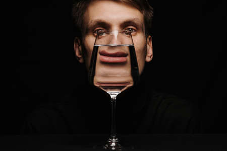 unusual portrait of a man looking through a glass of water