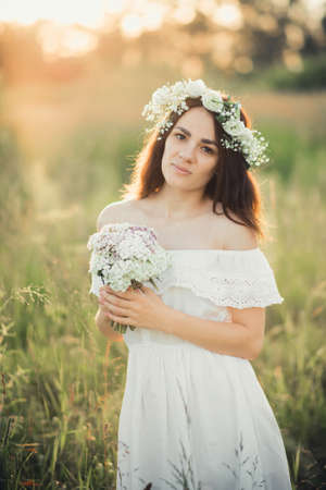 Caucasian happy girl in a white dress with a bouquet of flowers and a wreath in the summer