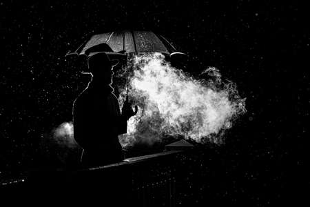 silhouette of a man in a hat under an umbrella at night in the rain in the city Standard-Bild