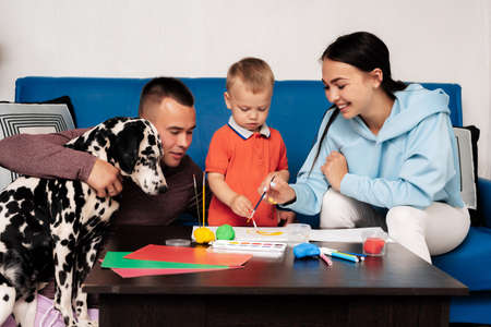 happy family with their son and dog Dalmatian sit at the table at home