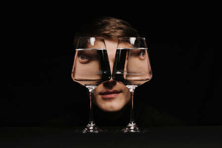 portrait of a strange man looking through two glasses of water