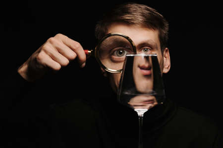 portrait of a man looking through a magnifying glass and a glass of water