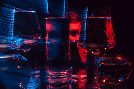 portrait of a strange man looking through glasses of water with blurring and red and blue neon lights 免版税图像