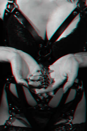butt plug in the hands of a girl on the background of her Breasts in a bra and a leather belt