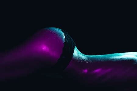Sexy of a girl in panties with water drops on her body close-up. Silhouette of a sporty slim female body