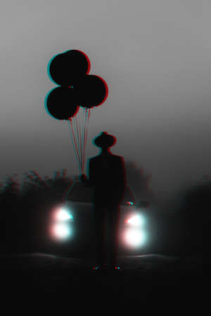 dark silhouette of a man in a hat with balloons in his hand Standard-Bild