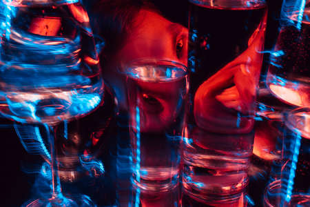 psychedelic portrait of a mad man schizophrenic looking through glasses of water Stockfoto