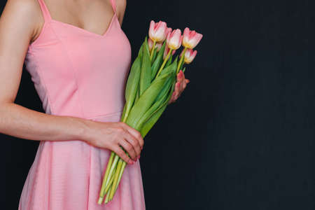 bouquet of pink tulips in women's hands. Greeting card template with copy space on background Banco de Imagens