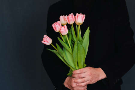 bouquet of pink tulips in the hands of a man in a black coat