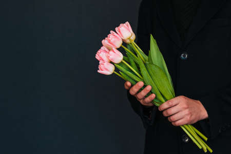 bouquet of pink tulips in the hands of a man in a black coat. Spring holiday greeting card template with copy space