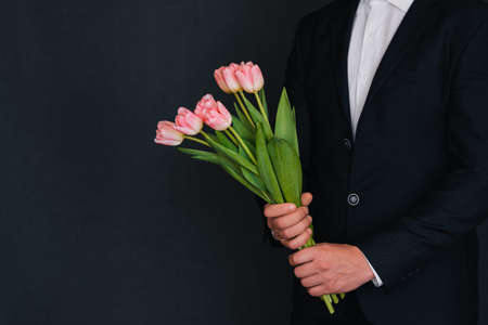 bouquet of pink tulips in the hands of a man in a blue suit. Spring holiday greeting card template with copy space