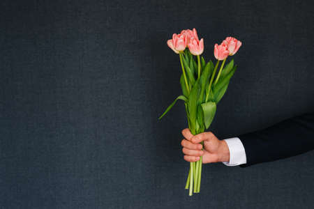man's hand giving a bouquet of pink tulips. Greeting card for international women's day with copy space