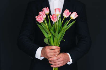 bouquet of pink tulips in men's hands in a blue suit for a gift for the spring women's holiday Banco de Imagens