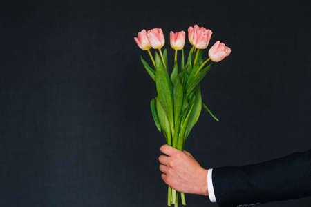 mans hand giving bouquet of pink tulips Banco de Imagens