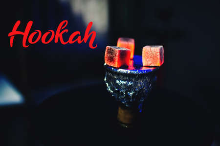 Hot red coals on foil on a hookah bowl close up