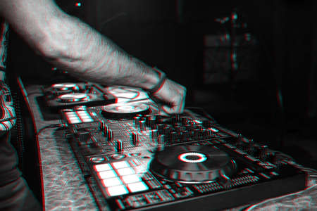 hands DJ playing electronic contemporary music on the mixer console at a concert in a nightclub