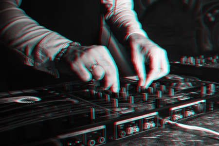 DJ in booth playing in nightclub on background of mixer