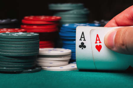 player reveals one pair of aces in poker against the background of playing chips on the green table