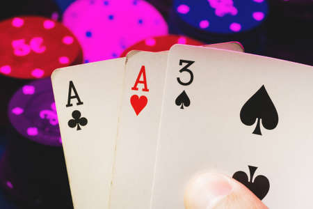 cards with one pair of aces in the hands of a poker player on the background of gaming chips