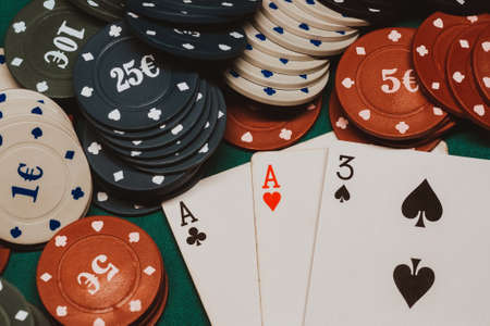 cards with one pair of aces in poker on the table with gaming chips in the casino